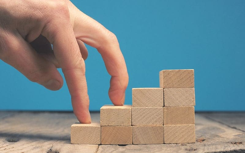 Getting career growth concept, Fingures walking on stacked wooden blocks stairs