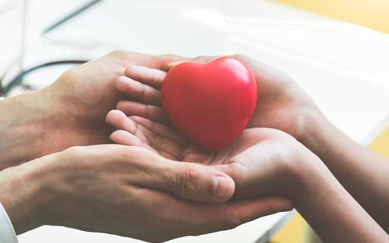 Doctor hands holding and giving red massage heart to patient